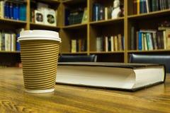 Pappers- kopp kaffe och bok på trätabellen Royaltyfri Foto