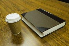 Pappers- kopp kaffe och bok på trätabellen Royaltyfria Bilder