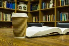 Pappers- kopp kaffe och bok på trätabellen Royaltyfri Fotografi