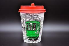 Pappers- kopp kaffe på en svart bakgrund, ett exponeringsglas av kaffe med ett rött lock arkivfoton