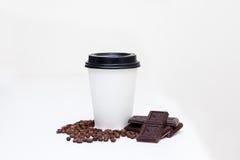 Pappers- kopp med kaffe och stycken av choklad, kaffebönor Arkivfoto