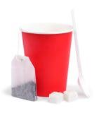 Pappers- kopp, teabag, sked och socker Arkivfoto