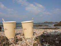Pappers- koppar med kaffe på bakgrunden av havet Arkivbilder