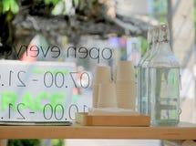 Pappers- koppar och vatten för kunder bredvid ett coffee shopfönster Arkivfoto