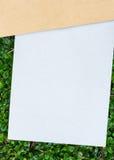 Pappers- kort och cardbroad som förläggas på grön bladmodell Arkivbilder