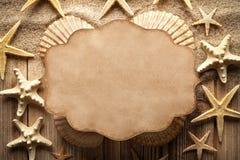 Pappers- kort och skal på sand och trätabellen royaltyfria bilder
