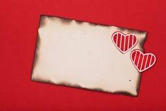 Pappers- och två hjärtor för tom grunge som bränns Fotografering för Bildbyråer