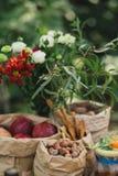 Pappers- påsar med muttrar, hasselnötter, röda äpplen och en grön bukett arkivfoton