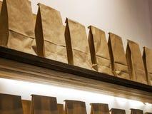 Pappers- påsar på hyllan arkivbild
