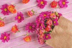 Pappers- påse med blommor på träbakgrund och att shoppa tid eller tid för försäljningar Arkivfoto
