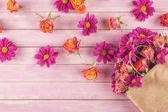 Pappers- påse med blommor på träbakgrund och att shoppa tid eller tid för försäljningar Arkivbild