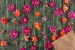 Pappers- påse med blommor på träbakgrund och att shoppa tid eller tid för försäljningar Royaltyfria Bilder