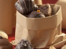 Pappers- påse med dekorativa choklader royaltyfria foton