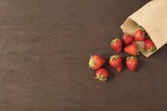 Pappers- påse med nya röda jordgubbar Nya jordgubbar i en liten påse på en trästil ytbehandlar Liten grupp av jordgubbar på royaltyfria bilder