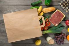 Pappers- påse mycket av olikt livsmedel på träbakgrund Arkivbild