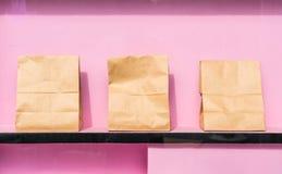 pappers- påse på rosa hylla arkivbilder