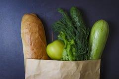 Pappers- packe mycket av mat på svart bakgrund Sund mat från lagret Grönsaker och bröd i packe från lagret Royaltyfri Bild
