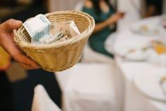 Pappers- pengar i ett träkorgslut upp arkivfoton