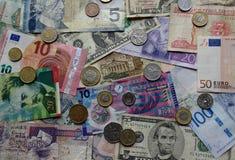 Pappers- pengar och mynt från över hela världen Arkivbilder