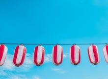 Pappers- röd-vit japanska lyktor Chochin som hänger på bakgrund för blå himmel Royaltyfri Bild