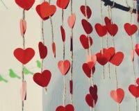 Pappers- röda hjärtor på rader från hampa Royaltyfria Foton