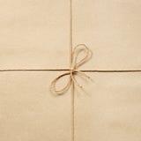 Pappers- rep som knytas på beiga för inpackningspapper Royaltyfri Foto