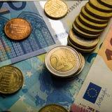 Pappers- sedlar av tio euro och mynt Arkivbild
