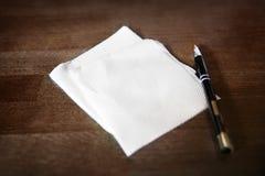 Pappers- servett och penna på tabellen arkivfoton