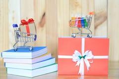 Pappers- shoppa påse och gåvaask med det röda bandet på modellminiatyrvagnen på böcker för jul och nyårsdagen eller hälsning arkivbild