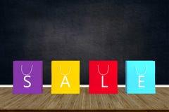 Pappers- shoppingpåsar av försäljningen på den wood tabellen med det svarta brädet tillbaka royaltyfri illustrationer