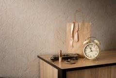 Pappers- shoppingpåse, läppstift och klockor Arkivfoton