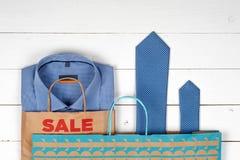 Pappers- shoppingpåsar, mäns skjortor och band på en vit träbakgrund Fotografering för Bildbyråer