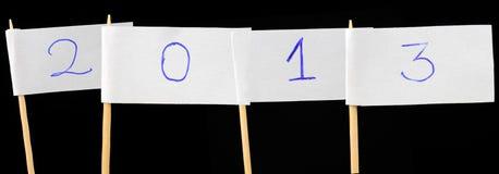 Pappers- sjunker med numrerar 2013 på svart bakgrund Arkivfoto