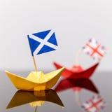 Pappers- skepp med den brittiska och scots flaggan Arkivbilder