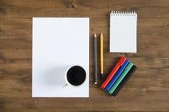Pappers- tomt ark, färgmarkörer, blyertspennor och en kopp kaffe Royaltyfri Foto