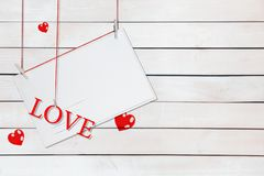 Pappers- vykort och ordförälskelse som hänger på röda trådar som omges av hjärtor med kopieringsutrymme på vit träbakgrund royaltyfria bilder