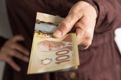 Pappersanmärkningar från Kanada dollar Främre sikt av handen för ` s för gammal kvinna royaltyfri foto