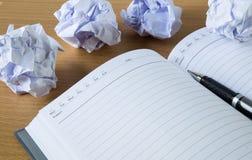 Pappersbollar och penna över det tomma vita arket Arkivbilder