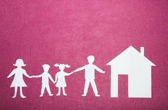 Pappersdiagram av familjinnehavet räcker nära hus Lycklig familj och hem- begrepp Förälder- och barn` s på rosa bakgrund Royaltyfria Foton
