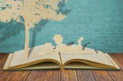 Papperssnittet av barn läste en bok Royaltyfri Fotografi