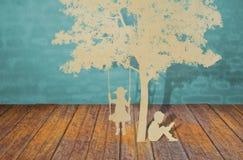 Papperssnittet av barn läste en bok under tree Arkivfoto