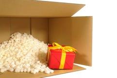 Pappsändningsask, smallred gåva inom, polystyrenemballagemuttrar Fotografering för Bildbyråer
