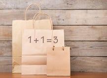 Pappshoppingpåsar med text ' 1+1=3' på träskrivbordet royaltyfri foto