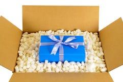 Pappversand-Lieferungskasten mit dem blauen Geschenk inner und den verpackenden Stücken des Polystyrens, Draufsicht Lizenzfreie Stockfotos