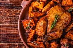Paprica e Herb Whole Chicken casalinghi con la patata dolce delle spezie Immagine Stock
