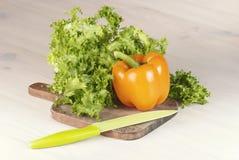 Paprica ed insalata sulla scheda di taglio fotografia stock libera da diritti