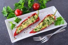 Paprica rossa cucinata forno farcita con formaggio, aglio e le erbe su un piatto bianco con il parcley e sui pomodori ciliegia Fotografia Stock Libera da Diritti