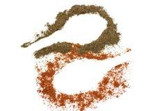 Paprika à terra vermelha e pimenta preta isoladas no fundo branco, fuga de uma colher imagens de stock