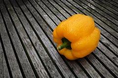 Paprika amarela esquecida que inclina-se e que desvanece-se em uma tabela de madeira fotografia de stock royalty free
