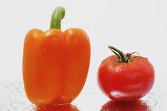 Paprika anaranjado fresco y tomate maduro Foto de archivo libre de regalías